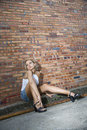 Woman against brick wall. Royalty Free Stock Images