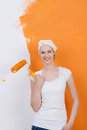 Woman against half painted wall smiling with paint brush orange Stock Photos