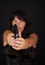 Woman aiming a gun against dark background with focus on the Stock Photo