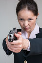Woman aiming a hand gun close up portrait of in business suit Royalty Free Stock Images