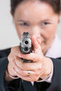 Woman aiming a hand gun close up portrait of in business suit Stock Photo