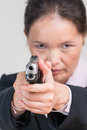 Woman aiming a hand gun close up portrait of in business suit at you Stock Image