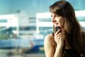 Woman in the airport young brunette is talking on mobile phone Royalty Free Stock Photography