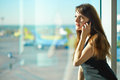 Woman in the airport young brunette is talking on mobile phone Royalty Free Stock Photo
