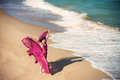 Woman in airy crimson dress on the beach full length portrait of a beautiful girl dancing Stock Photography