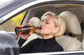 Woman alcoholic drinking as she drives the car from a bottle of alcohol Royalty Free Stock Photo