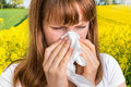 Woman with allergy on yellow field sneezing in tissue