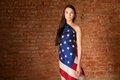 Woman in the american flag on background of a brick wall Stock Image