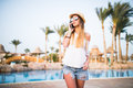 Woman answer on phone call near swiming pool on summer vocation Royalty Free Stock Photo
