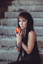 Woman with apple in abandon building black dress Stock Photo