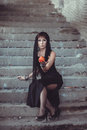 Woman with apple in abandon building black dress giving Stock Photography