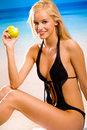 Woman with apple on beach Royalty Free Stock Photos