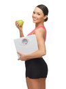 Woman with apple and weight scale picture of sporty Stock Image