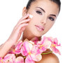 Woman applying cosmetic cream on face beautiful with pink flowers body isolated white Stock Photo