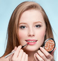 Woman applying cosmetic lipstick brush Stock Photos