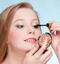 Woman applying cosmetic mascara brush Stock Photos