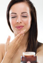 Woman applying cream beautiful on her chin Stock Images