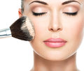 Woman applying dry cosmetic tonal foundation on the face closeup portrait of a using makeup brush Royalty Free Stock Photos