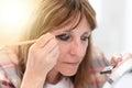 Woman applying eyeshadow powder, light effect Royalty Free Stock Photo