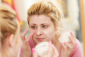 Woman applying face cream with her finger Royalty Free Stock Photo
