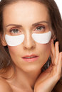 Woman applying gel eye mask Stock Photography