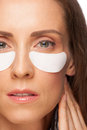 Woman applying gel eye mask Stock Images