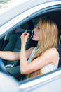 Woman applying make-up while driving car. Royalty Free Stock Photo