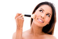 Woman applying makeup with a brush isolated over white background Stock Images