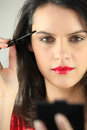 Woman applying mascara brunette carefully Stock Photos