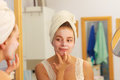 Woman applying mask cream on face in bathroom Royalty Free Stock Photo