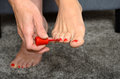 Woman applying red nail varnish to her toenails using an applicator brush close up view on her hand and bare feet Stock Images