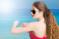 Woman applying sunscreen on her arm on the beach Stock Photos