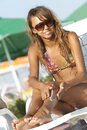 Woman applying suntan lotion Stock Photos