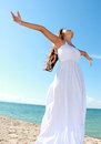 Woman with arms open enjoying her freedom relaxing at the beach wear long white dress Royalty Free Stock Photos