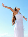 Woman with arms open enjoying her freedom relaxing at the beach wear long white dress Royalty Free Stock Images