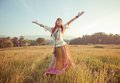 Woman with arms outstretched hippie in golden field on sunset Stock Images