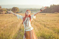 Woman with arms outstretched hippie in golden field on sunset Royalty Free Stock Images