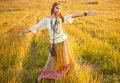 Woman with arms outstretched hippie in golden field on sunset Royalty Free Stock Photography