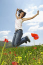 Woman with arms raised jumping in poppy field portrait of excited young Stock Photo