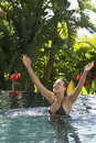 Woman with arms raised in outdoor swimming pool attractive young Royalty Free Stock Images