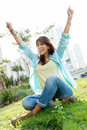 Woman with arms up casual sitting at the park Stock Image