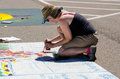 Woman artist creating outdoors a is art at the th chalk the block event in st joseph michigan Stock Photo