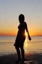Woman as silhouette by the sea Stock Photo