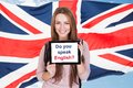 Woman asking do you speak english young holding digital tablet in front of british flag Royalty Free Stock Photos