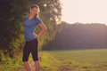 Woman athlete pausing to relieve her back pain holding hand lower with a grimace while out training in the Royalty Free Stock Photos