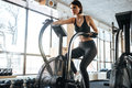 Woman athlete sitting and training on bike in gym Royalty Free Stock Photo