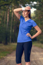 Woman athlete wiping sweat from her forehead onto wristband as she pauses during training exercises on a forest track Stock Photo