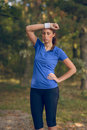 Woman athlete wiping sweat from her forehead onto wristband as she pauses during training exercises on a forest track Royalty Free Stock Images