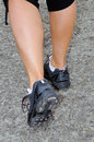 A woman with an athletic pair of legs going for a jog runner feet running on road closeup on shoe fitness Stock Image