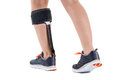 Woman in athletic sneakers wearing brace on calf close up rear view of person support around leg muscle studio with white Stock Photo